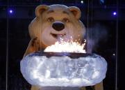 Misha the Bear extinguishes the Olympic flame, Sunday, Feb. 23, 2014, in Sochi, Russia. (AP Photo/Charlie Riedel)