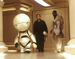Marvin the Paranoid Android (voice by Alan Rickman) escorts Arthur Dent (Martin Freeman) and Ford Prefect (Mos Def) to the bridge of the Heart of Gold, a prototype ship powered by the Infinite Improbability Drive in the 2005 film adaptation of The Hitchhiker's Guide to the Galaxy.  (Photo:  TheGuardian.com)