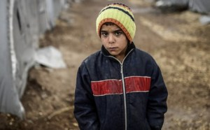 A Kurdish refugee boy stands during a rainy day at the Rojova Camp, in Suruc, a rural district of Sanliurfa Province, on October 30, 2014. Heavily armed Kurdish peshmerga fighters were on their way by land and by air, joining militias defending the Syrian border town of Kobane, also known as Ain al-Arab, from the Islamic State group after setting off from Iraq. Kobane's Kurdish defenders have been eagerly waiting for the peshmerga since Turkey last week said it would allow them to traverse its territory to enter the town. AFP PHOTO/ BULENT KILIC (Photo credit should read BULENT KILIC/AFP/Getty Images)