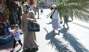 On October 6 in Jerusalem, a Muslim woman shopped for Eid ul-Adha while a group of Jewish women carried home palm fronds for the upcoming Sukkot holiday. (Photo: Simone Wilson, Jewish Journal)
