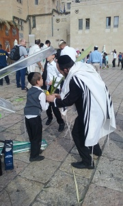 An Orthodox Jewish father teaches his son how to wave the lulav.